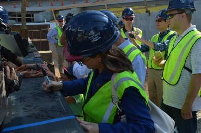 Chamber COO Sharon Mason autographs the beam that will fly high above the ground at a project elevation at 1120 feet 4 inches.